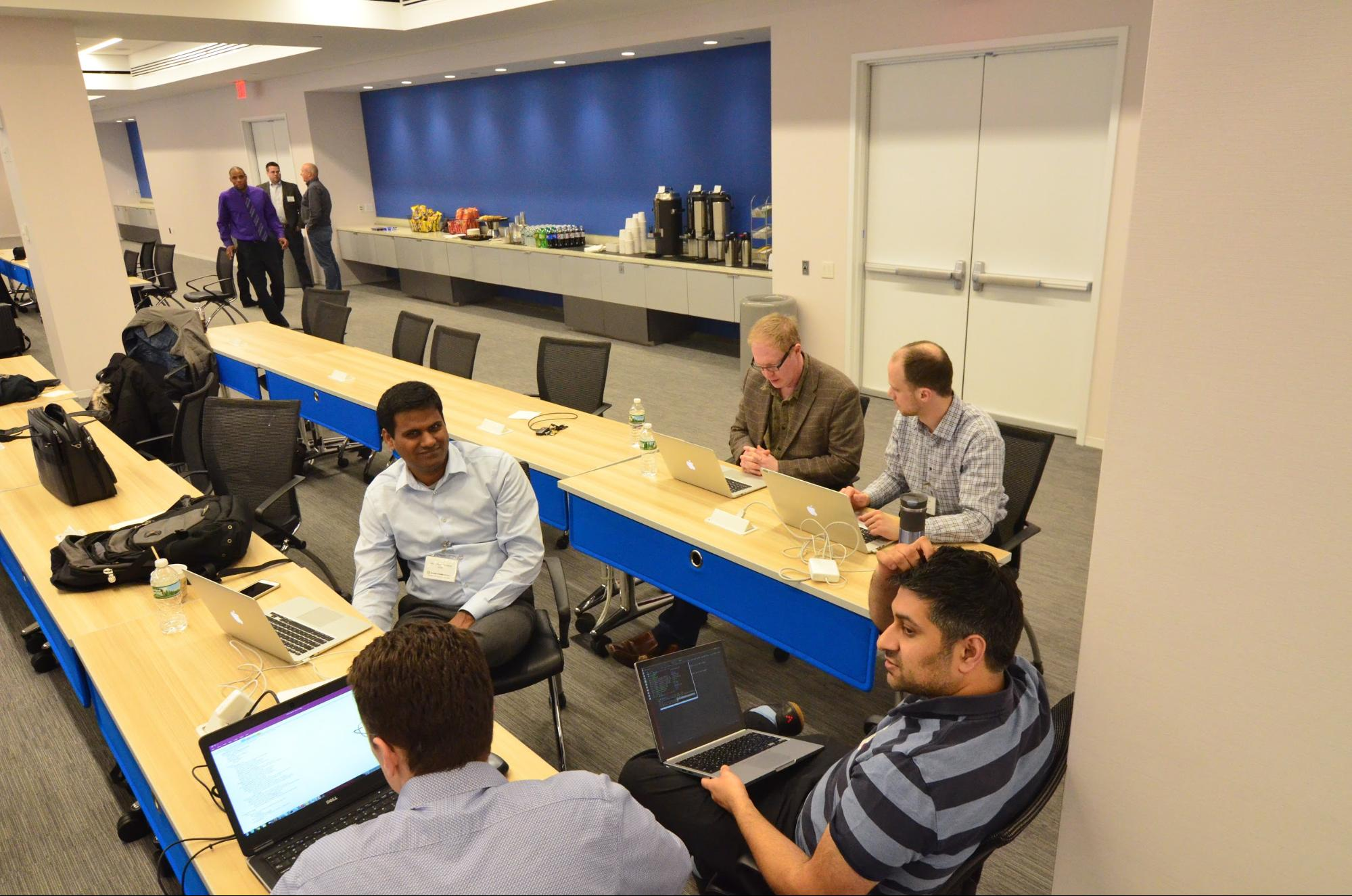 At work. Stan Liberman (on the far right) discusses the use case with Damien Briggs (on the far left)
