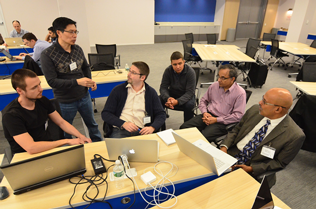 A team from IBM, DAH, and Altoros works on combining code. Group leader Robert Fajta is in yellow shirt in center.